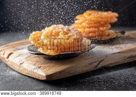 Indian Sweets Jalebi On A Wooden On A Dark Background. Powdered Sugar Is Poured On Top.