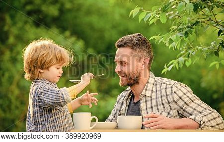 Dad And Boy Eat And Feed Each Other Outdoors. Ways To Develop Healthy Eating Habits. Feed Your Baby.