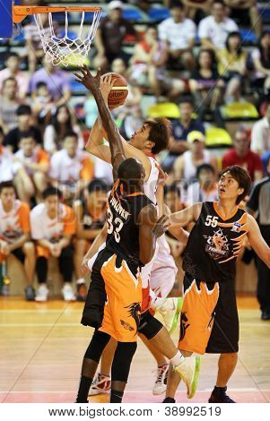 KUALA LUMPUR - OCTOBER 28: Dragons' Chee Li Wei (white) scores against Firehorse's defense (black) in a Malaysia National Basketball League match on October 28, 2012 in Kuala Lumpur, Malaysia.