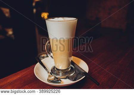 Hot Latte Macchiato Coffee With Caramel Arts On The Top Serving With Tall Clear Glass.