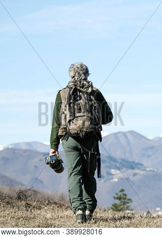 Hiker Senior Man With Backpack And Camera Walking On The Mountain Path - Active Traveler Pensioner W