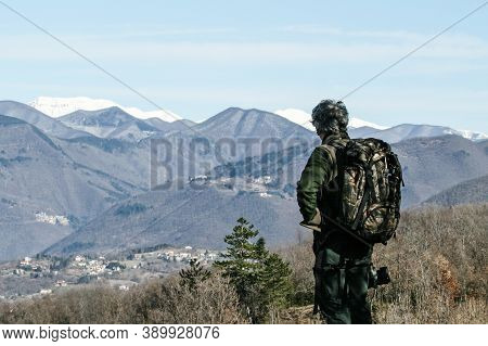 Hiker Senior Man With Backpack Standing On The Mountain Top - Active Traveler Pensioner With Grey Ha