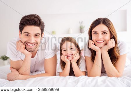 Photo Of Charming Young Lady Guy Little Girl Happy Family Lying Sheets Leaning Hands Head Toothy Smi