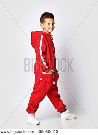 Boy Advertises A Fashionable Sportswear Model For Children Posing For The Camera In A Red Warm Jumps