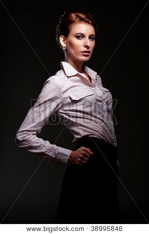 sexy and stylish woman in white shirt posing over dark background