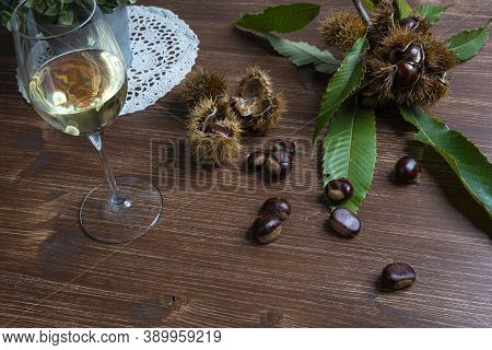 Chestnuts And A Glass Of White Wine On A Wooden Table In Autumn