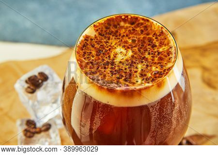 Cold Drink Or Nitro Coffee Drink In A Glass With Bubble Foam And Ice, Top View.