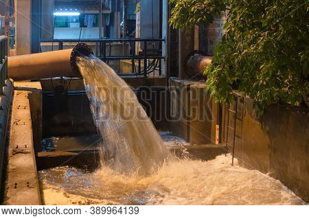 A Drain Pipe Tube, Sewage Or Sewage Discharges Waste Water Into A River From Factory Industry. Water