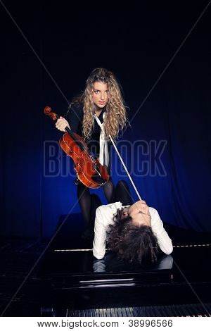 Two beautiful young sexy women posing with violon and piano