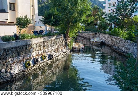 Small Water Canal In Turkish City. City Landscape With Canal, Boats And Colorful Reflections On The