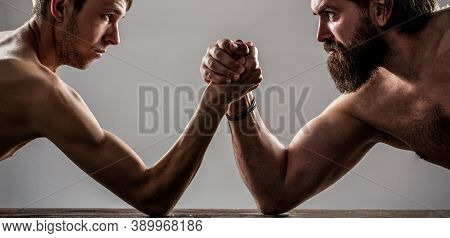 Two Mans Hands Clasped Arm Wrestling, Strong And Weak, Unequal Match. Heavily Muscled Bearded Man Ar