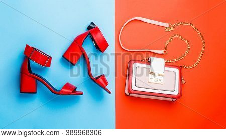 Stylish Red Womens Leather Sandals Shoes. Woman Bag, Sandals On Red And Blue Background Isolation. L