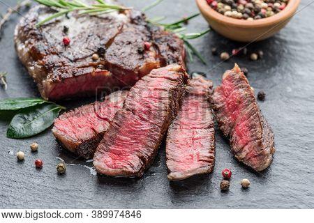 Medium rare Ribeye steak with herbs on graphite board.