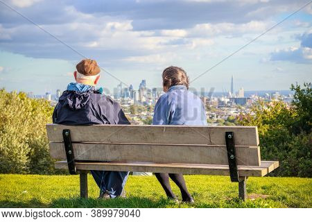 London, Uk - October 5, 2020 - Back View Of Senior Couple Looking Over London City Skyline From Parl