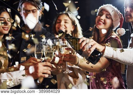 Pouring Champagne. Group Of Cheerful Friends Celebrating New Year Indoors With Drinks In Hands.