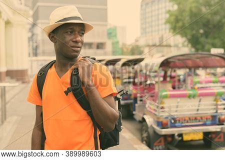 Young Black African Tourist Man Thinking While Holding Backpack And Sightseeing At Railway Station W