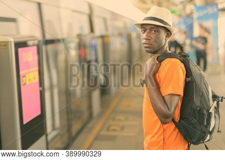 Young Black African Tourist Man Waiting For The Train At Bts Sky Train Station Of Bangkok Thailand