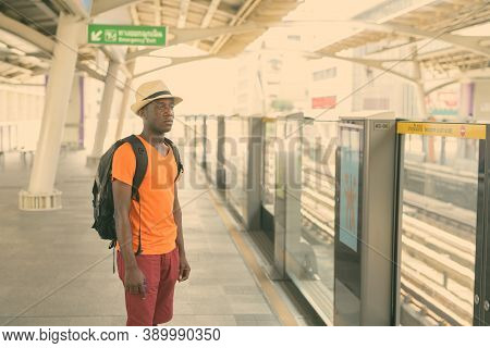 Young Black African Tourist Man Standing And Thinking While Waiting For The Train At Bts Sky Train S