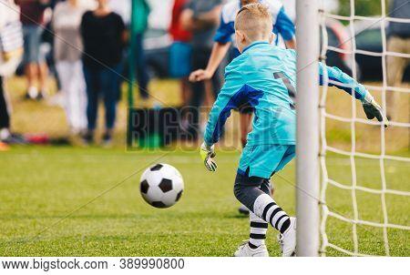 Boy Football Goalie In Action. Young Soccer Goalkeeper Running Towards Soccer Ball. Child Goalie Soc