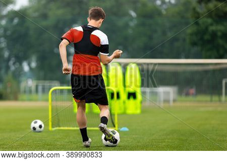 Teenager On Football Training With Ball. Youth Footballer Practicing On Training Field. Young Footba