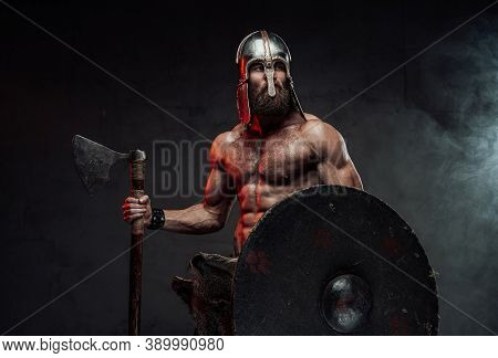 Muscular And Bearded Nord Fighter With Naked Torso And Helmet Posing Holding Shield And Axe In Dark