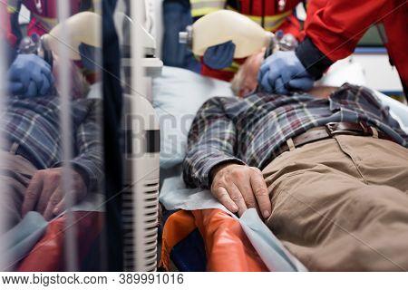 Focus Of Elderly Patient Lying In Ambulance Car While Paramedics Doing Cardiopulmonary Resuscitation