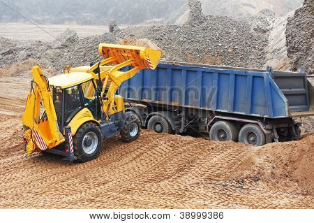 Wheel loader Excavator with backhoe loading sand into dumper truck at eathmoving works in construction site quarry