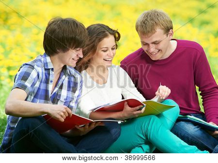 Group of three young students studying with note books in spring outdoors
