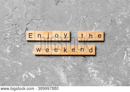 Enjoy The Weekend Word Written On Wood Block. Enjoy The Weekend Text On Cement Table For Your Desing
