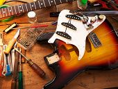 Sunburst electric guitar on guitar repair desk or in a repair work shop. Neck and pickguard detached. Double cutaway solid body guitar. Shallow depth of field. poster