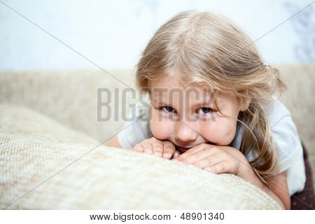 Sly Caucasian Girl Hiding Her Face In Sofa Pillows