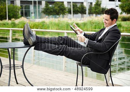 Junger erfolgreicher Geschäftsmann entspannt im Freien mit tablet