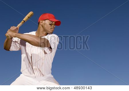 Confident African American baseball batter waiting to strike the ball