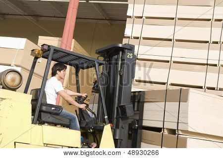 Side view of a young male laborer with forklift stacking wood