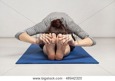 Young woman excersising yoga in a gym