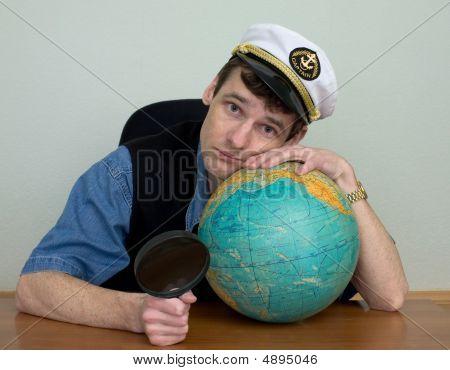 Guy In A Sea Cap With A Globe