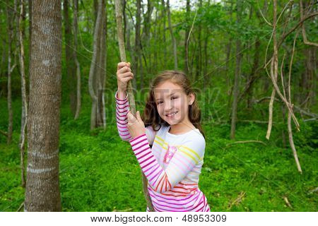 Happy children girl playing in forest park jungle with liana smiling