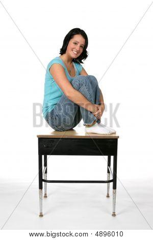 Pretty Teenage Girl Sitting On The Top Of A School Desk