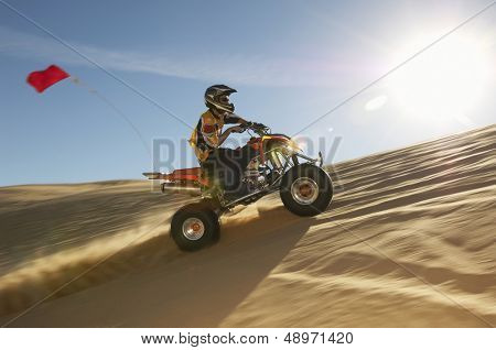 Side view of a man riding quad bike in desert on a sunny day
