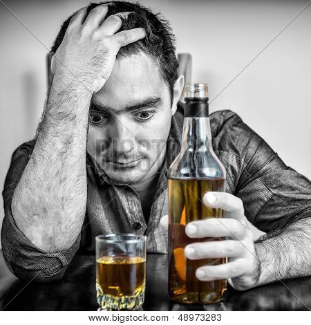 Black and white image of a desperate drunk hispanic man drinking
