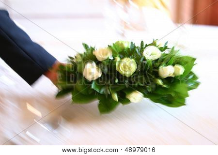 Waiter putting flowers on table.