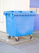 Clean blue plastic rubbish bin in urban area with copyspace poster
