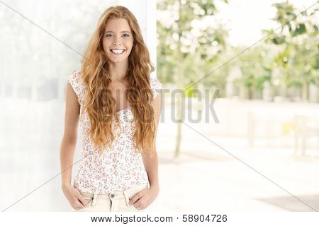 Summer portrait of long hair gingerish woman, smiling happy, looking at camera. Plenty of copyspace.