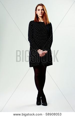 Full-length portrait of a young beautiful woman in casual dress on gray background