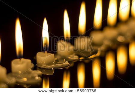 lots of candles burning in the dark
