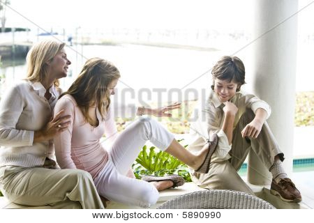 Family sitting on terrace together, teenager girl kicking younger brother poster