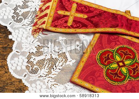 Antique red damask maniple on a white lace catholic priest surplice