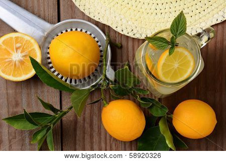 Fresh Squeezed Lemonade on a rustic wooden table with lemons, sun hat and juicer. Horizontal format with an oldtime feel, shot from a high angle.
