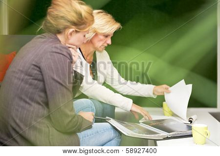 Paparazzi like view of two women discussing a plan during a covert meeting, seen through a plant in a green environment