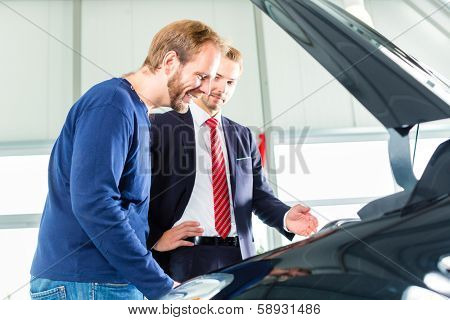 Seller or car salesman and client or customer in car dealership presenting the engine performance of new and used cars in the showroom, the men looking under the hood